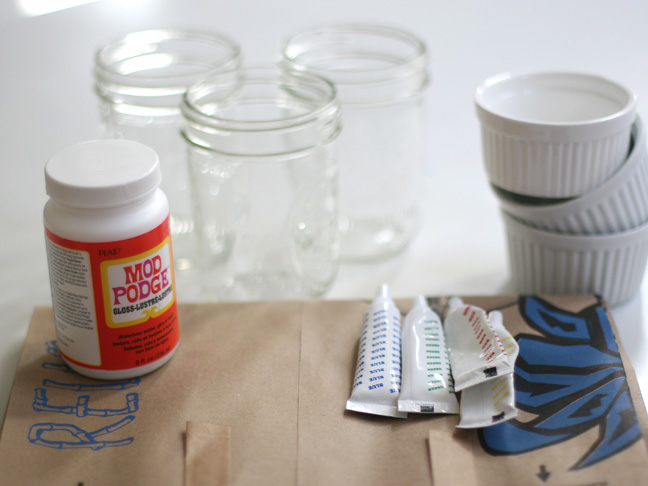 a bottle of mod podge shown with assorted food coloring tubes and empty ramekins in the background