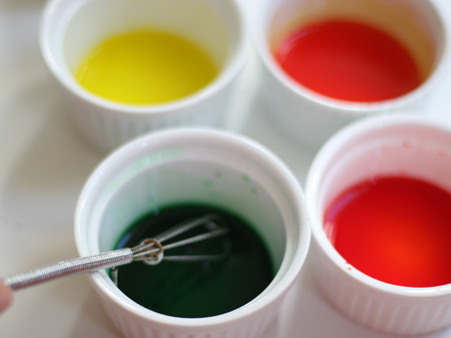 4 ramekins each being whisked with yellow, green, red and blue food coloring