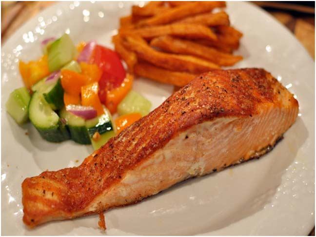 Cooked salmon plated with a vegetable salad and sweet potato fries