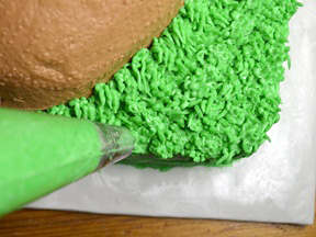 Piping grass on to the cake with green icing