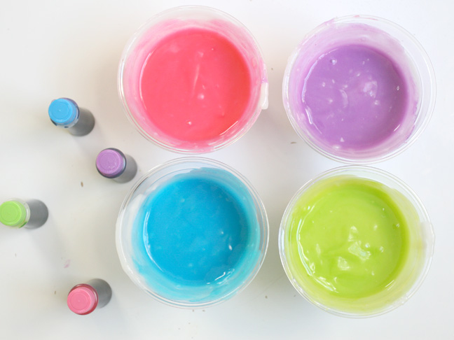 homemade pink, green, blue and purple finger paint in individual plastic cups
