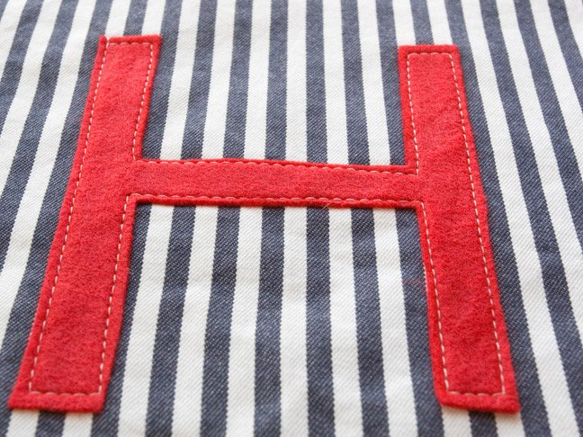 """a close up of the """"H"""" sewn on to the white and blue pinstriped fabric"""