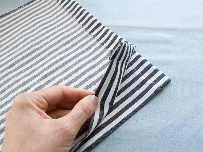 the fabric is folded over in half with one end being held up