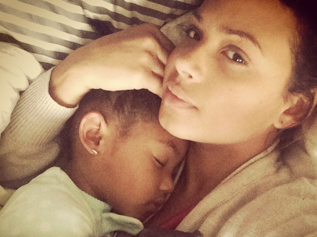 Christina Milian without makeup laying in bed with her child