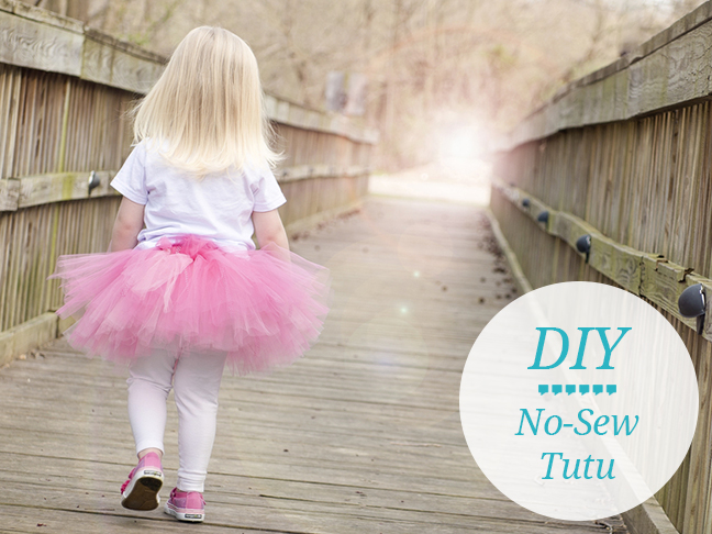 little blonde girl running away with her back turned wearing a white tshirt and pink homemade tutu
