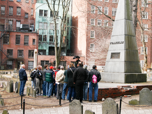 A shot of tourists from the back standing around the Boston Freedom Trail