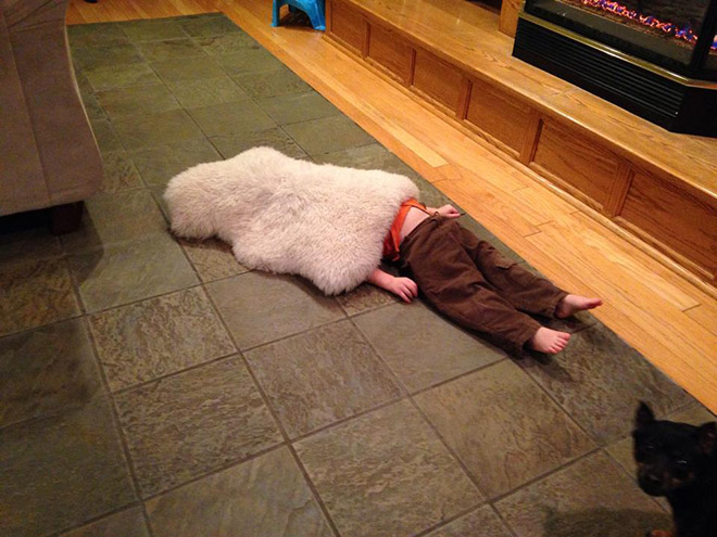 child laying on the floor with a cover