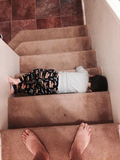 child laying flat on stairs
