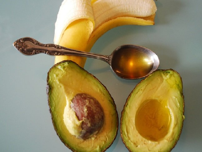 peeled banana pictured with a spoon of honey and halved avocado
