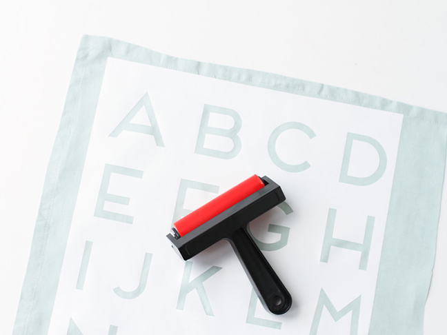 Attach stencil to tea towel and roll over it with a brayer.