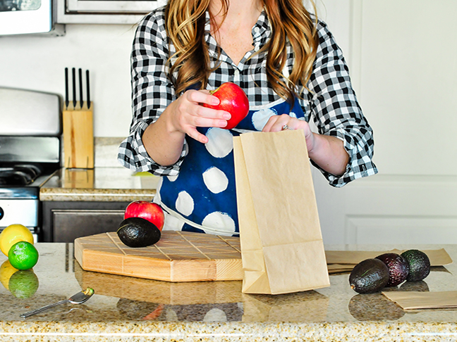 woman putting apple in paper bag