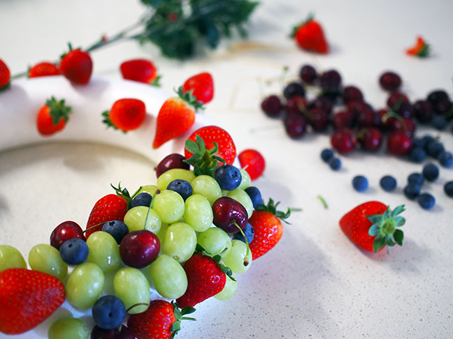 Continue placing fruit into the wreath with toothpicks until filled.