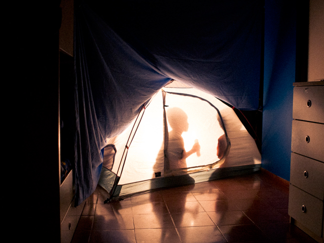 Children camping inside the house in a tent