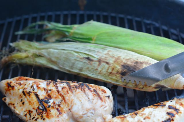 Placing presoaked grill corn husks on the grill