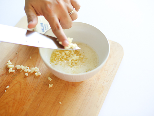 adding garlic to melted butter