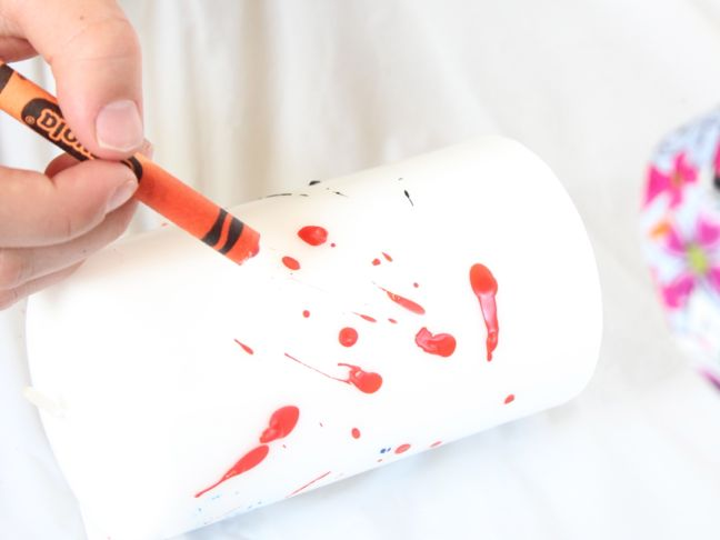 decorating candle with melted orange crayon