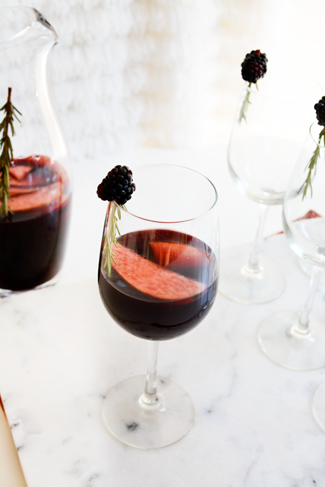 red sangria in white glass with blackberry garnish