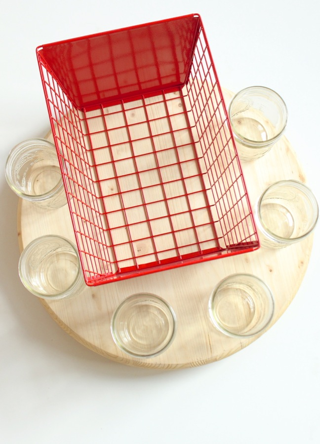 red-metal-basket-and-mason-jars-on-a-wood-round