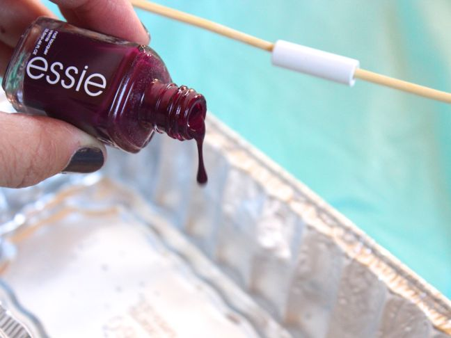 pouring burgundy nail polish into water