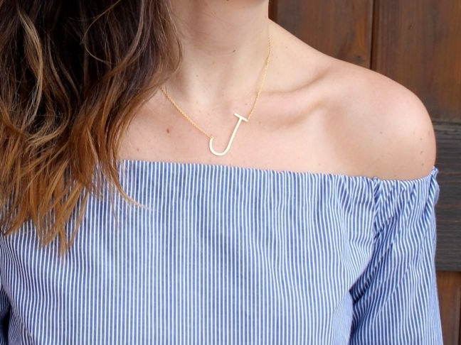 woman-wearing-a-blue-and-white-striped-off-the-shoulder-shirt-gold-j-necklace